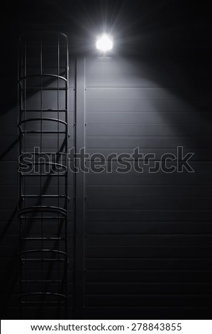Fire emergency rescue access escape ladder stairway roof maintenance stairs night lantern lamp light shadows industrial building wall vertical closeup copy space background dark grey black - stock photo