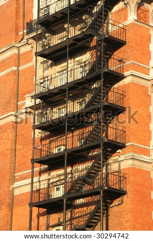 Fire escape on an old apartment building in the afternoon sun - stock photo
