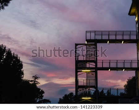 Fire escape or external metal stairway on the exterior facade of a multistorey building silhouetted against a colourful sunset sky in shades of pink and purple - stock photo