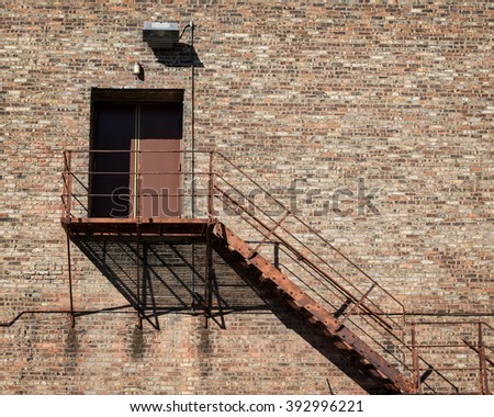 Fire escape staircase on outside of brick building - stock photo