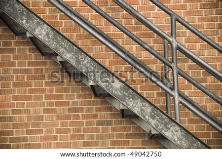 Fire escape stairs against a brick wall background - stock photo