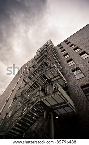 Fire escape stairs on an old building in perspective - stock photo