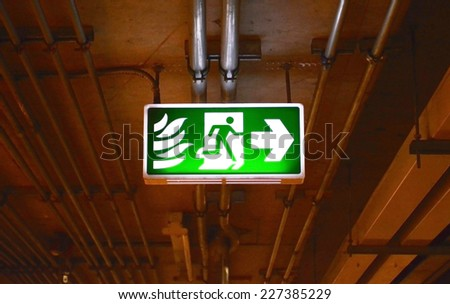 Fire exit sign in car park building - stock photo