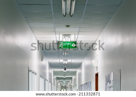 Fire exit sign in factory - stock photo