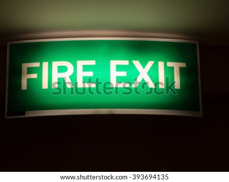 Fire exit sign. Light green emergency fire exit sign in the office/hotel shows people way out. - stock photo