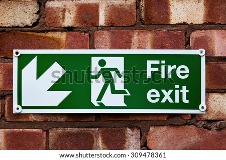 Fire exit sign on the red clay brick wall  - stock photo
