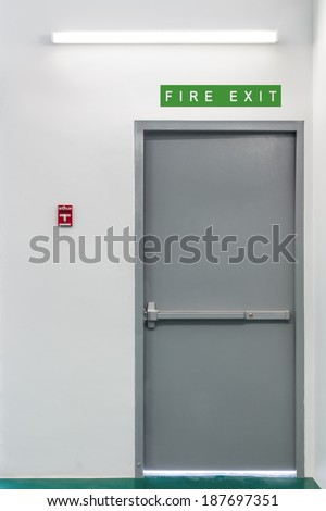 Fire exit steel door for evacuation in case of fire, with fire alarm pull switch on the wall near the door - stock photo