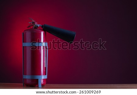 Fire extinguisher on a red background. - stock photo