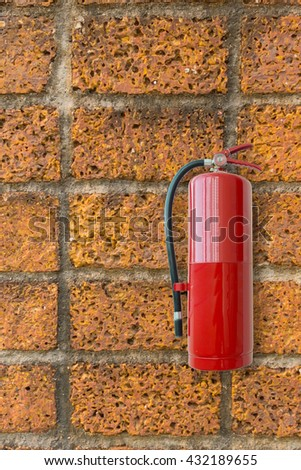 Fire extinguisher on brick wall. - stock photo