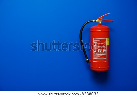 Fire extinguisher on the blue wall - stock photo