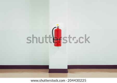 Fire extinguisher on white wall, ready for use. - stock photo