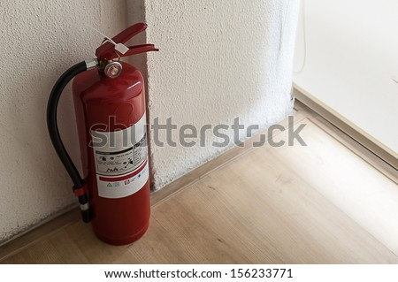 Fire extinguisher on wood floor in corner room - stock photo