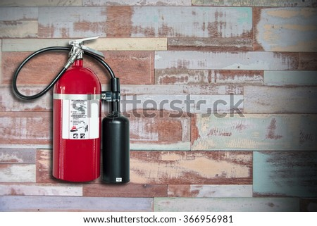 Fire extinguisher on wooden wall background