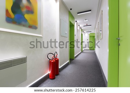 Fire extinguishers in hotel corridor - stock photo
