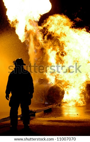 Fire fighter and burning propane tank NOTE there is slight halo caused by the intense back lighting on the fireman's right side and the noise isn't really noise it is water droplets in the air - stock photo