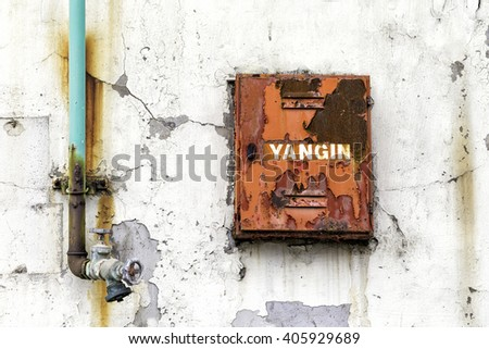 Fire fighter box for fire hose and water valve on an weathered wall of the old building. On the red box it is written YANGIN in Turkish, which means FIRE in English. - stock photo