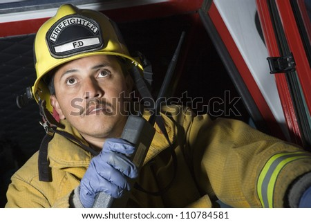 Fire fighter having conversation on walkie-talkie - stock photo