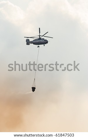 Fire fighter helicopter with loaded water basket on it's way to a fire. - stock photo