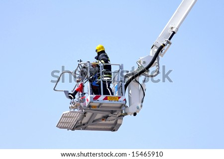 Fire fighter in big and tall crane - stock photo