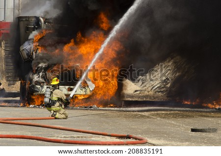 Fire fighters respond to a semi truck and silage fire at a dairy farm - stock photo