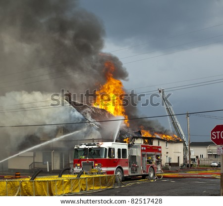 fire fighters responding to fire in a large building engulfed in flames - stock photo