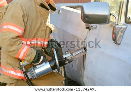 Fire fighters use a hydraulic rescue tool to remove the door of a pickup