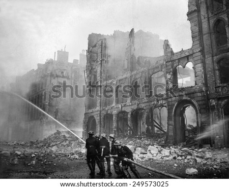Fire fighting during WW2 Battle of Britain. Firemen at work in bomb-damaged street in London, after Saturday night raid, ca. 1941. - stock photo