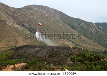 Fire fighting helicopter dousing burnt area of countryside - stock photo