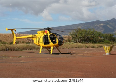 Fire-fighting helicopter on ground with water bucket - stock photo