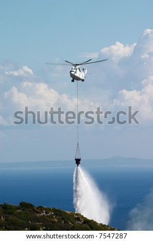 fire fighting helicopter put out forest fire - stock photo