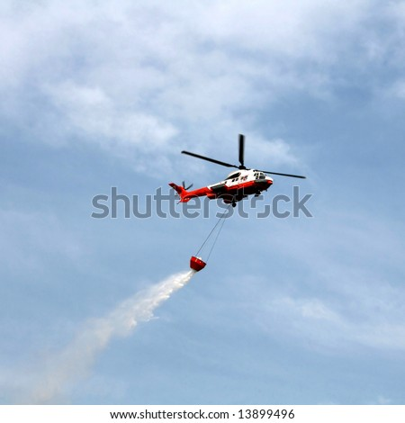 Fire fighting helicopter with bucket against blue sky - stock photo