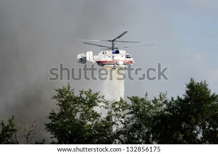 fire fighting helicopters drops water on the fire - stock photo
