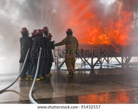 Fire fighting team training with real fire - stock photo
