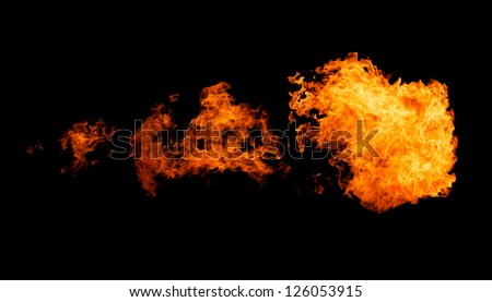 Fire flame bursting in one direction - isolated on black - stock photo