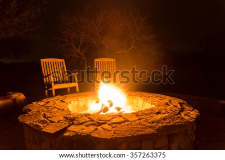 Fire flame in a fire pit and two empty wood chairs next to it with dark forest at the back - stock photo