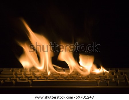 Fire flame on keyboard isolated on black background - stock photo