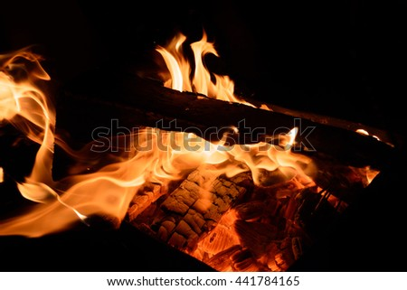 Fire flowing through wood on a black background - stock photo