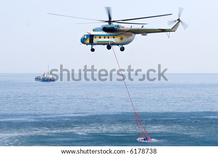 fire helicopter taking water from the sea to its special tank - stock photo