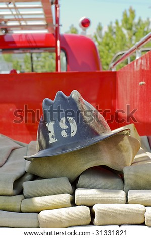 Fire helmet on hoses in vintage truck - stock photo