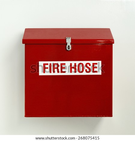 Fire hose box in bright red hung on white wall - stock photo