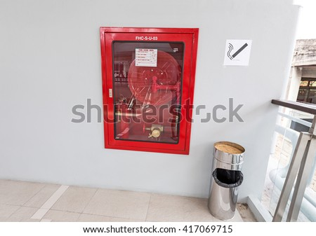 Fire hoses packed inside of red emergency box at the wall-smoking area