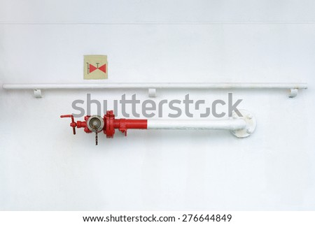 fire hydrant on a metal wall with a sign - stock photo