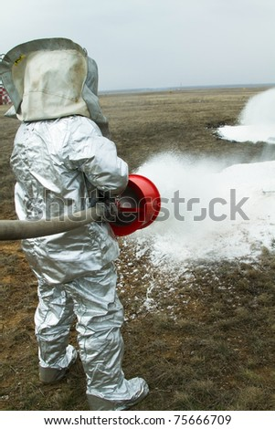 Fire in a silver protective suit puts voozgoranie foam. - stock photo