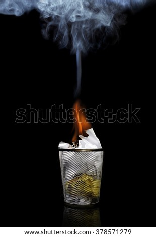 Fire in a Wastebasket or Trashcan on a Black Background - stock photo