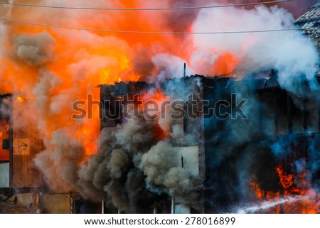Fire in an old wooden house - stock photo