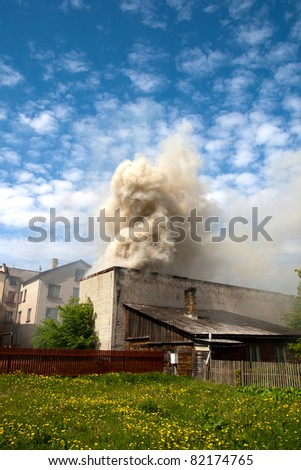 fire in city building, with white smoke to the blue sky - stock photo