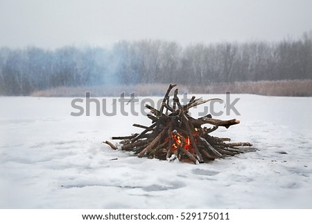 Fire in falling snow on frozen lake