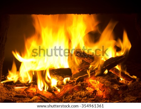 Fire in fireplace. Closeup of firewood burning in fire - stock photo
