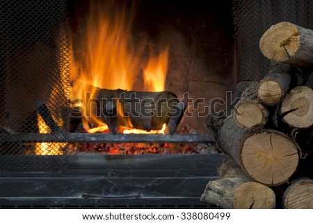 fire in fireplace with a pile of log firewood - stock photo
