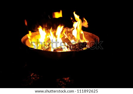Fire in outdoors fire pit - Camp fire - stock photo